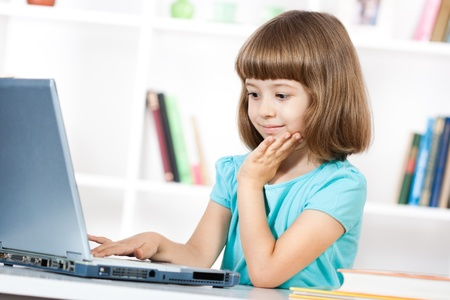 Little girl using laptop and smiling