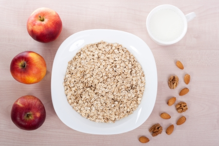 Plate of oats with apples,almonds and nuts and cup of milk