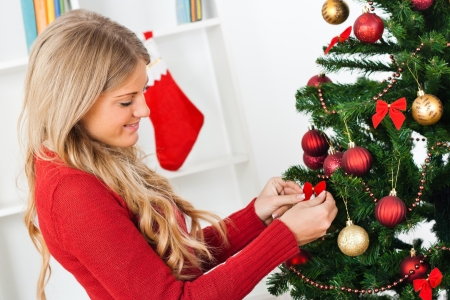 Bella giovane donna che decora l'albero di Natale