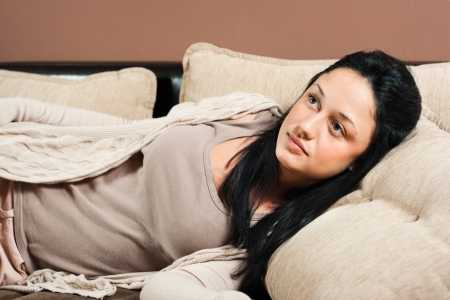 Beautiful young woman lying on sofa and thinking photo