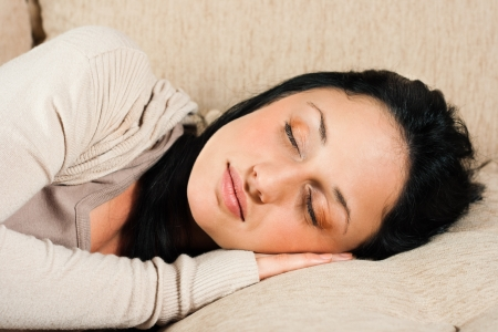 Beautiful young woman is sleeping on the sofa Stock Photo