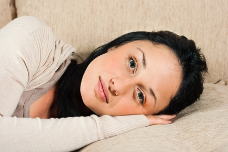 Young woman lying on the sofa and looking at camera