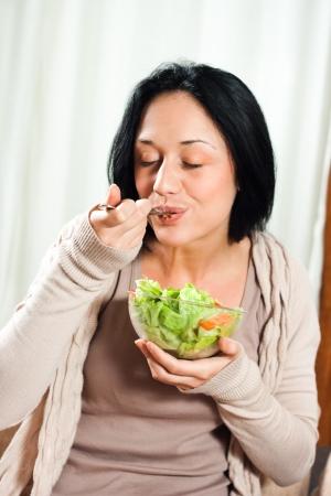 Giovane bella donna mangiare insalata
