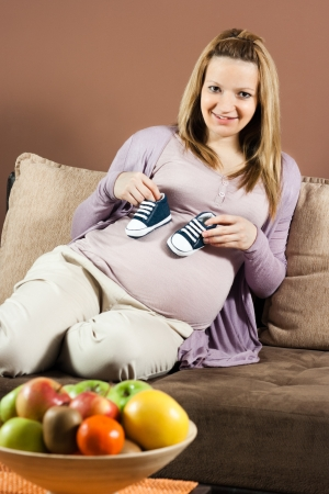 Smiling pregnant woman sitting on sofa and holding baby booties