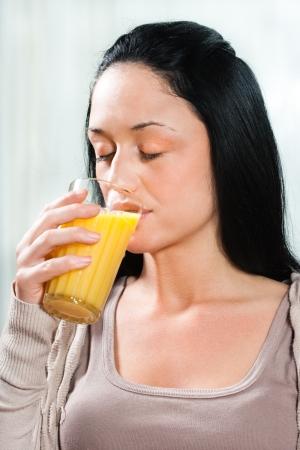 Bella giovane donna che bere succo d'arancia Archivio Fotografico