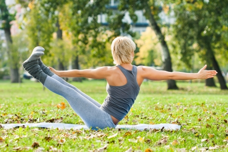 Young woman practicing yoga in the park   photo