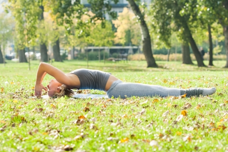 Young woman practicing yoga in the park Stock Photo