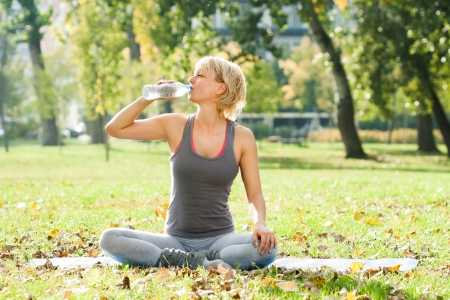Giovane donna seduta nel parco acquatico e potabile dopo l'esercizio