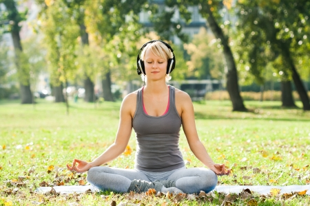Young woman is listening music in the park and relaxing after exercise photo