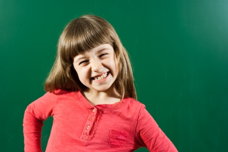 Portrait of cheerful little girl smiling in front of blackboard