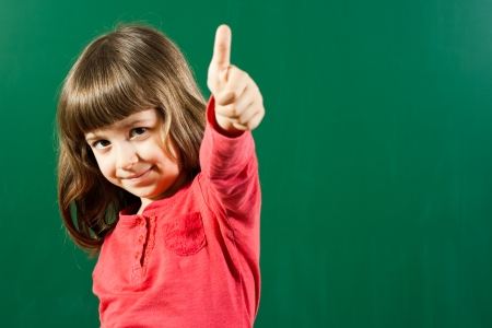 Portrait of little girl giving thumbs up in front of blackboard Stock Photo