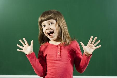 Little girl is having fun in front of blackboard  Stock Photo