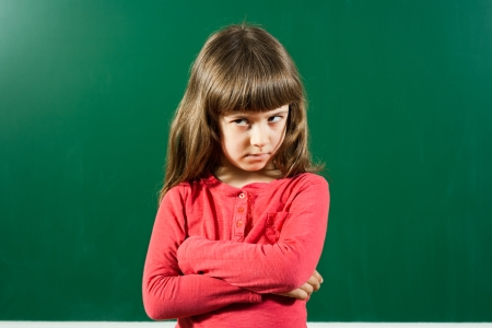 Portrait of angry little girl in front of blackboard  Stock Photo
