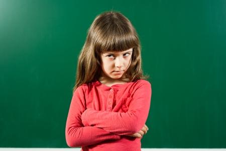 Ritratto di arrabbiato bambina di fronte alla lavagna