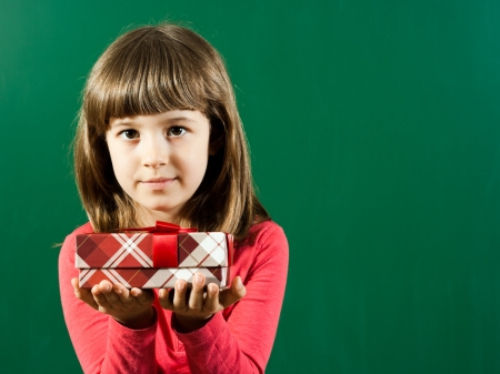 Beautiful little girl holding gift box in front of blackboard photo