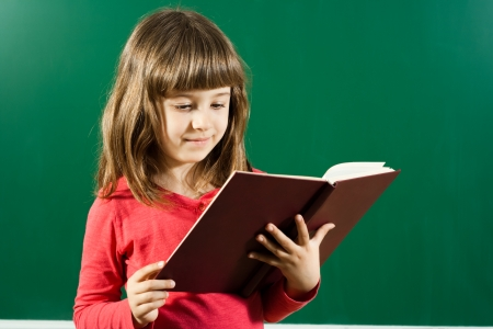 Cute little girl is standing in front of blackboard and reading a book
