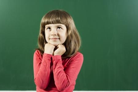 Carino bambina sta pensando di fronte alla lavagna