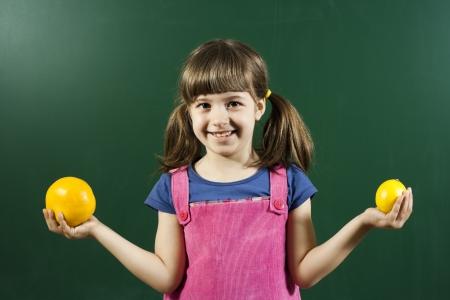 Cute little girl holding citrus fruit in front of blackboard
