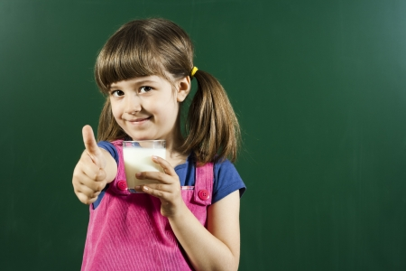 Cute little girl holding glass of milk with thumbs up