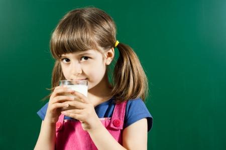 Cute little girl drinking milk in front of blackboard