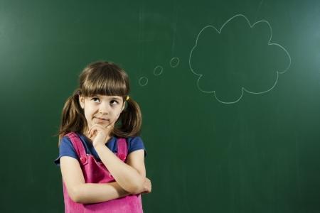 Cute little girl is thinking in front of blackboard  Stock Photo