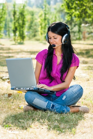 Beautiful woman with headphones sitting in the park and using laptop   photo