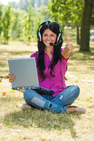 Beautiful woman using laptop and headset and showing thumb up photo