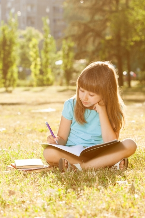 Little girl sitting in the park and writing her homework,intentionally toned