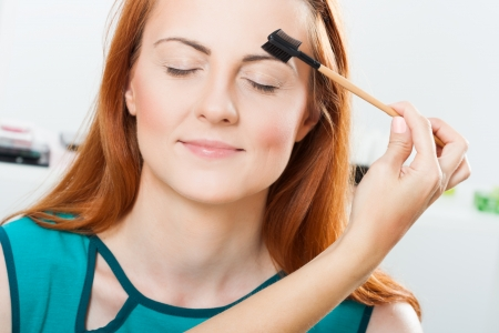 make up artist: Photo of make up artist grooming eyebrow of a beautiful woman Stock Photo