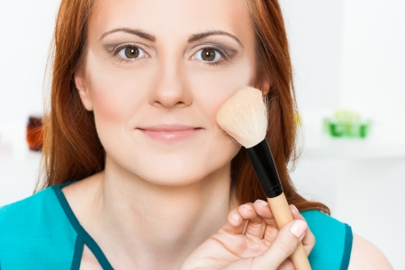 Photo of make up artist applying blusher to beautiful woman photo