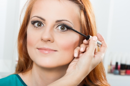 Photo of make up artist applying mascara on a beautiful woman