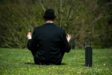 Businessman sitting on the grass in park and meditating