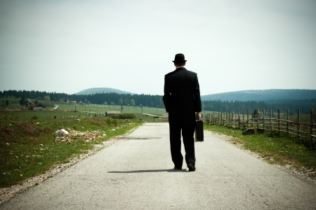 Businessman walking on country road and thinking