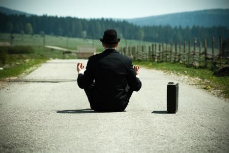 Businessman seduto sulla strada di campagna e la meditazione