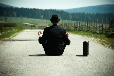Businessman sitting on country road and meditating  photo