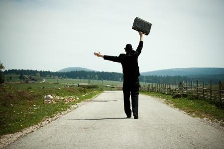 田舎で歩く幸せなビジネスマン