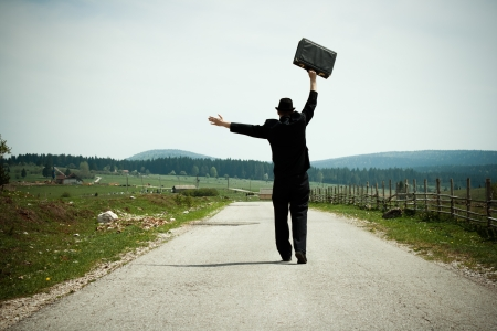 Happy businessman walking in the countryside Stock Photo