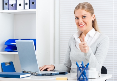 Portrait of beautiful young businesswoman showing thumbs up