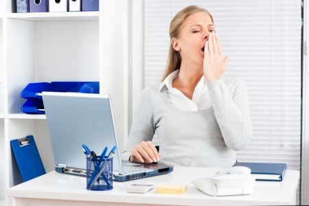banging: Exhausted young businesswoman yawning at work