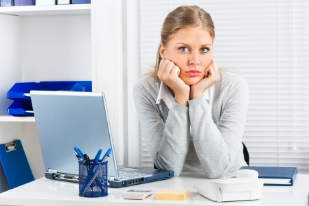 Bored businesswoman sitting in her office   photo