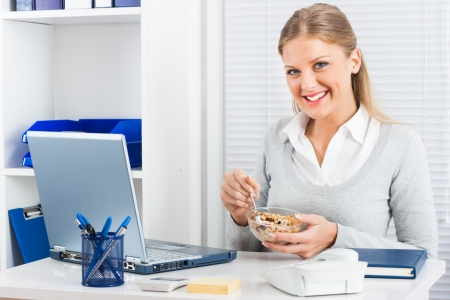 Young businesswoman is eating cereals for breakfast at\ work