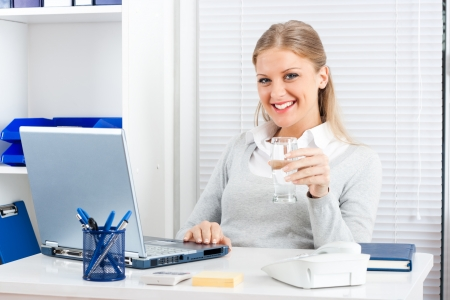 Portrait of businesswoman holding glass of water photo