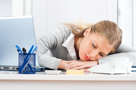 Beautiful tired business woman sleeping at work  photo