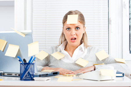 businesswoman: Young businesswoman with too much work to do  Stock Photo