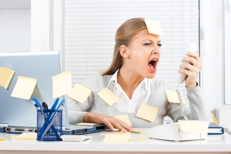 Young businesswoman shouting on telephone at her office  photo