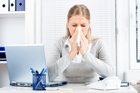cold and flu: Young business woman sneezing while working in office