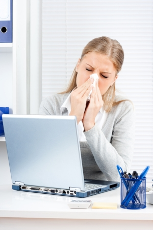 Young business woman sneezing while working in office photo