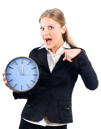 Beautiful businesswoman pointing at wall clock  Stock Photo
