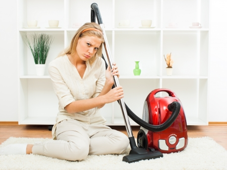 Young housewife sitting in living room with vacuum cleaner tired of everyday chores  photo