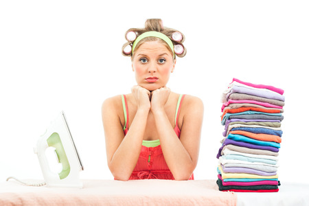 only one young adult woman: Young housewife is unhappy because she has got a lot of laundry for ironing  Stock Photo